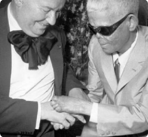 Raoul Follereau stringe le mani a un cieco