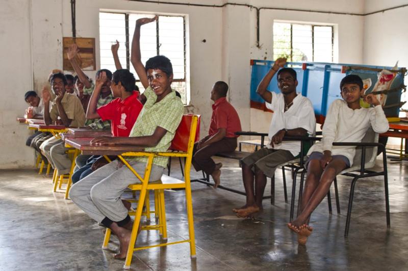 Ragazzi in aula che alzano le mani