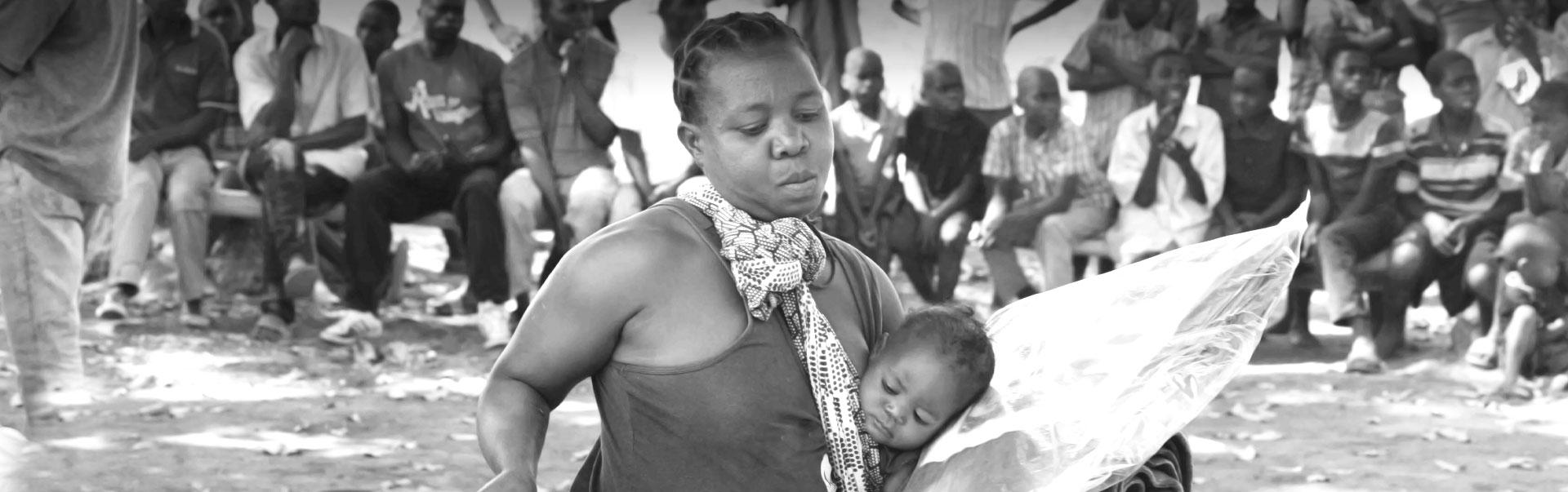 Copertina pagina emergenze: donna con bambino e materiali donati da AIFO