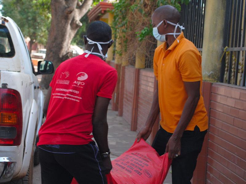 Volontari AIFO trasportano sacco di riso durante emergenza COVID