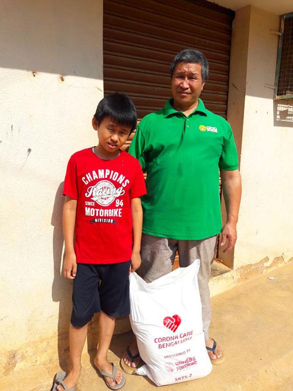 Padre e figlio in Mongolia con un sacco di riso AIFO del kit Covid