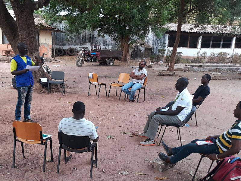 Gruppo di persone sedute a distanza su sedie mentre un volontario spiega loro materiale informativo su Covid 19