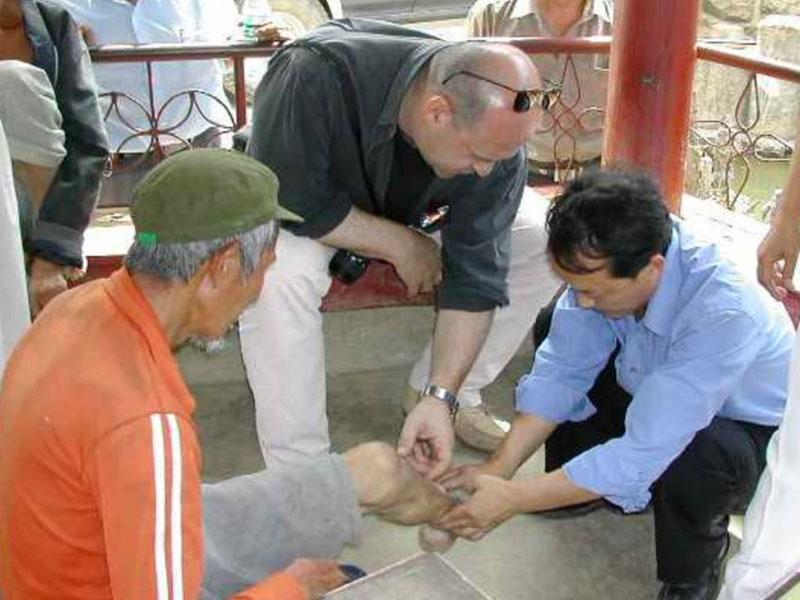 Volontari che aiutano un anziano nel progetto in Yunnan